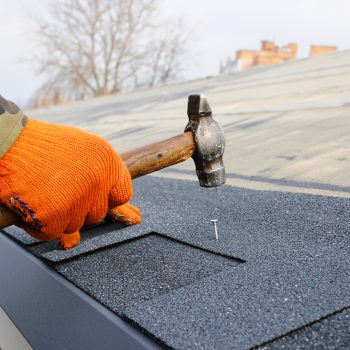 Roof repair contractor working on replacing roof shingles
